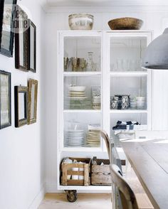 Tall kitchen cabinet—Anna's grandfather used old windows as doors to create the kitchen's tall cabinet, which stores the family's favourite china. Free of knick-knacks and fussy arrangements, the display is approachable yet still beautiful. The cabinet's oversized industrial casters add edge.
