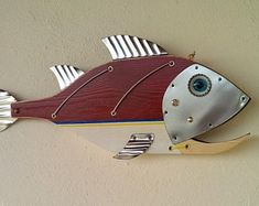 Fish made with Wood, Metal,Glass, Handmade by Unikos Arts Give your wall a upcycled beach steampunk theme with one of a kind original distressed Fish wall art sculpture. Hanging point provided at back for ease of wall hanging Dimensions D x W x H 8 in Fish Wall Art, Fish Art, Fish Fish, Fish Sculpture, Wall Sculptures, Steampunk Theme, Metal Fish, Whale Art, Unique Wall Decor