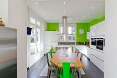 Green with envy: This French SieMatic kitchen pairs clean white modern cabinets with neon green walls and chairs for a pop-art vibe | via IDKREA
