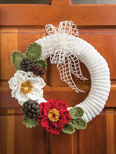 Poinsettias, pinecones and evergreen leaves make up this Holiday Wreath. Winter issue, Crochet World. designer, Lynn Wasylkevych