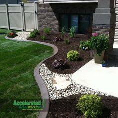 River rock and flagstone step stone allow access through the landscaping bed and break up the primary use of mink mulch.  The dark mulch really makes the green and purple shrubs/perennials pop in the landscaping bed.