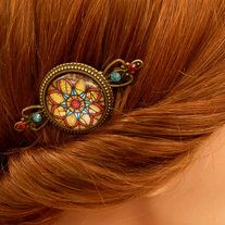 This festive hair comb is made of bronze metal. On the front, a solid-crafted jewelry setting is replaced with a handcrafted glass cabochon, which shows a beautiful mandala motif. The eye of the frame and the sides of the hair comb decorated with Swarovski rhinestones in red and turquoise.   Th...