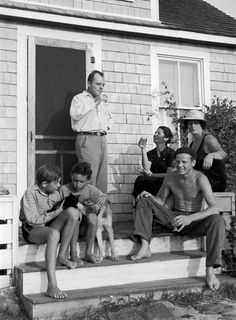 Jackson Pollock (seated R) sitting on the steps of painter Thomas Hart Benton's summer home with Rita Benton (white hat) and author Coburn Gilman (standing) in 1937.  Alfred Eisenstaedt