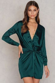 Get the highest luxe levels in this mini dress! The Fame And Lust Silk Dress by Lioness comes in the color teal and features a deep front plunge, a twisted tie detail, long sleeves with a teal button at each cuff, a high slit in the front, and is not lined underneath. Wear this gorgeous piece over a pair of skinny black jeans with black pumps and a lace bra underneath!