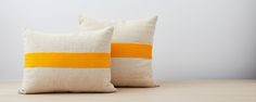 100% wool pillows hand loomed in Tunisia by local artisans, with vegetable dyed horizontal contrast stripe in orange, blue or yellow. Sold with insert.