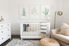 Modern gender neutral nursery design with a white, beige, and gray color scheme featuring modern botanical triptych wall art prints, white crib, gray and white striped throw blanket, beige upholstered chair, fur pillow, rattan pouf, and moroccan shag area rug - Baby Nursery Ideas & Decor Akin Design Studio | Iron Horse Nursery