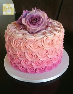 Pink ombre piped buttercream rosettes cake. Topped with 3 large handmade purple shaded roses.
