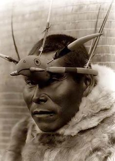 Edward S. Curtis.  The photograph presents Eskimo man, head-and-shoulders portrait, wearing headdress consisting of a protruding headband around the crown of his head, feathers, and a wooden bird head in front.