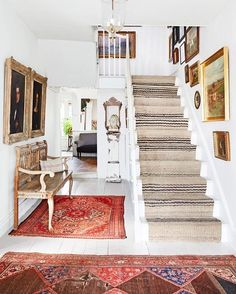 Bright contrasting rugs with white floors as the source of warmth in the room