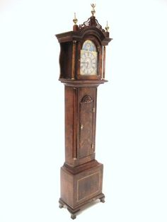 "A very fine flamed mahogany grandfather clock with tombstone door decorated with shell-carving, the base sporting a diagonally striped inlay, reeded column and quarter columns, and delicately carved fretwork cornice surmounted by brass finials. 8"" at top of finial. This is a working clock. Z"