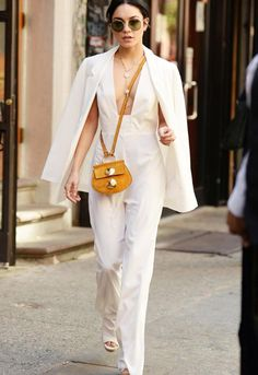 Vanessa wears an all white blazer & jumpsuit, accessorized with a long necklace, small gold hardware bag, open toe wedges, and oversized oval sunglasses for an easy and fun one piece look.