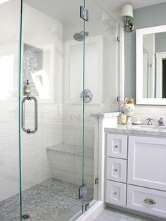 A glass-enclosed shower with white tile walls and a gray mosaic tile floor is adjacent to a marble vanity with white under-counter cabinets.