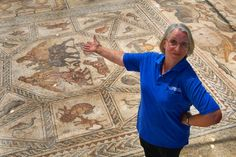 Israeli archaeologist Miriam Avissar kneels alongside an ancient Roman mosaic as it is revealed some 13 years after it was first discovered in the ruins of a 4th century AD building, on July 1, 2009 in Lod in central Israel. The beautiful 1,700 year old mosaic floor, which is regarded as one of the most magnificent and largest ever revealed in Israel, was first uncovered in 1996 during a project to upgrade the city's sewage system.