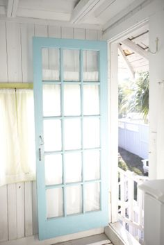 white wood and a bright blue door. The Mermaid Cottages. Tybee Island, Georgia. photo Ingrid Rorem