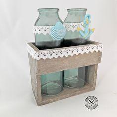 Tengerparti témájú vázaszett - 4799 Ft  Csipkével és tengeri motívumokkal díszített üvegvázák fa tartóban. Szolid és hangulatos dekoráció néhány szál virágnak. A tároló méretei: magasság: 10,5 cm, szélesség: 13 cm, mélység: 7,5 cm A vázák méretei: magasság: 16 cm, átmérő: 3 cm