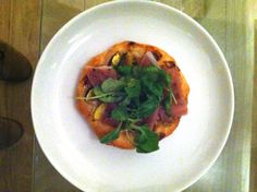 Italian: mini pizza appetizer with puff pastry, fig, prosciutto, honey, pepper, olive oil and watercress