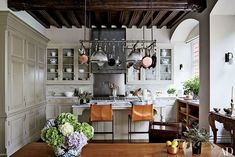 The kitchen's pot-rack light fixture is by Ann-Morris, and the stools are by…
