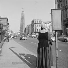 Daughter of Charity waiting for a bus outside the Rotunda Hospital on Parnell Street, Dublin, Ireland (pre-1964).