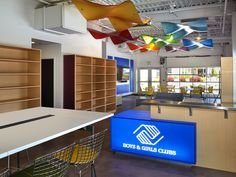 Varia Shapes on the ceiling in pops of color combine with a lit desk in this Boys & Girls Club in Idaho.