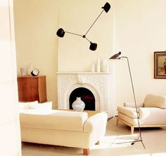 Serge Mouille.  Interesting use as feature wall light above fireplace.