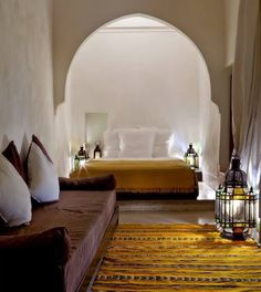 carved wood furniture, warm colours berber carpet, moroccan lamp or pendant, glass coloured lanterns, and alcoves