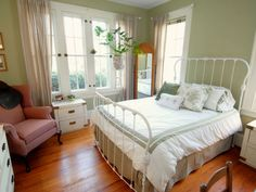 A wrought iron bed frame is the perfect centerpiece, along with farmhouse dressers, ladderback chairs and soft paint colors adds country charm.