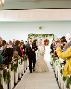 """Pine garlands and magnolia leaves decorated the pews at Emmanuel United Methodist Church, while a """"Christmas Cannon"""" by Trans-Siberian Orchestra played as the bride and her father, William, entered the ceremony. Seeing the doors open and his bride walk in was Michael's most memorable moment of the day."""