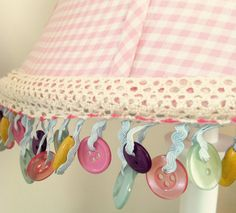 Add some whimsy to a lamp shade with button trim and hot glue.