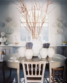 Kitchen Photo - An oval table topped with white confit pots