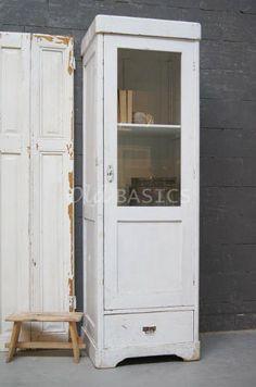 Smalle kast 10117 - Oude houten smalle kast in een witte kleur. Door het glas in de deur heeft de kast een frisse uitstraling. Achter de deur zitten twee verstelbare legplanken, er is ook nog een extra plank bij. Onderin een lade.