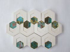 Wall tiles made from plaster and oxidized brass. The brass triangles and hexagons show the various stages of oxidation. An experiment with the natural process of metal by letting it oxidize and colour-bleed.   post-graduation work 2013 ● © 2015 L...