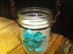 This candle hand poured and made with pure soy, embellished with a turquoise sola flower, and wrapped with grapevine wire. This candle is poured in a 16 oz jar and is ready to hang indoors or out !!! This is perfect for your rustic chic wedding whether to light a room or light an outdoor pathway. Just simply hang on a hook, end of chair, or a shepherds hook.