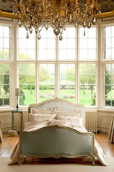 windows and light that surround this french bed are so great! The Chandelier is opulent & beautiful as well.