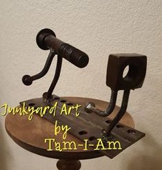 """Junkyard Art by Tam-I-Am. An oversized nut and bolt come together to make  """"The Chase."""" Repurposed. Scrap metal art."""