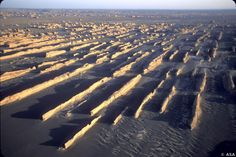 ASA Spain Yardangs in the Gobi Desert. These yardangs are near Yumenguan, China. Yardangs are ridges of rock created by wind erosion. They form in dry areas where strong prevailing winds blow in a single direction, carrying abrasive particles that erode the rock to form the ridge shapes. In this case, sand is the abrasive material doing the eroding.