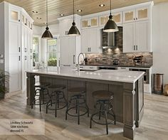 Glass inserts in stacked cabinetry provide a beautiful accent in this transitional kitchen featuring painted Oak kitchen cabinets. A unique layout gives the space a personality all its own, while the Riverbed island exudes a warm elegance as it contrasts against the Pearl perimeter.