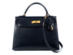 Ca. 22 x 28 x 10 cm. Lederhandtasche in Dunkelblau mit goldfarbenen Beschlägen. Innenraum mit einem Reißverschluss- und zwei Steckfächern. Anbei...