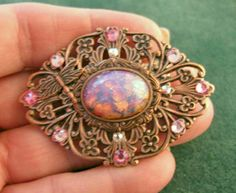 This piece is the perfect reprise of a late Victorian sash brooch, brought up to 21st century.  The center stone is a Czech glass faux Mexican fire opal.  Vintage Pink Opal Cabochon, Crystal, and Antique Copper Filigree Pin by Beadlady5, via Flickr    components available at bsueboutiques.com....including the stone.