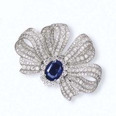 A SAPPHIRE AND DIAMOND BROOCH    Designed with a detachable oval-cut sapphire weighing 26.99 carats within a brilliant-cut diamond surround to the brilliant-cut diamond pierced ribbon bow, accompanied by fittings to form a ring and smaller diamond bow pendant brooch, mounted in white gold