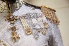 [Майлон] Как и полагалось наследному принцу, будущему королю, Майлон имел обширный гардероб нарядов, сшитых по его фигуре и желаниям. Большинство костюмов, что предназначались для светских событий, были сшиты из светлых тканей с золотыми или рубиновыми нитями. Каждый сюртук был сродни произведению искусства.
