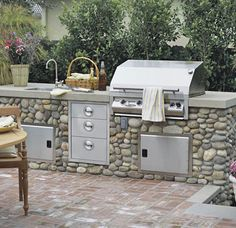 The outdoor kitchen's gas grill, bar sink, and stainless steel drawers and vents are built into a rock-face cabinet topped with a concrete counter. The combination of textures adds artistic interest. Just as with an indoor kitchen, this is where guests ar Small Outdoor Kitchens, Outdoor Kitchen Bars, Outdoor Kitchen Design, Outdoor Rooms, Outdoor Living, Outdoor Decor, Backyard Kitchen, Backyard Patio, Backyard Ideas
