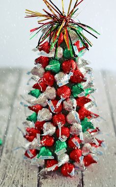 """In the holiday spirit for a festive centerpiece, but aren't super crafty? These """"Kiss""""-mas Tree Centerpieces made with Hershey's Kisses are super easy to make and are a fun project to work on with kiddos!"""