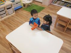 """After practicing pouring water, children in the toddler class help each other clean up. By doing this, the children learn practical life skills and cooperation. Cleaning the table also requires hand-eye coordination, an essential first step in learning our Montessori """"work."""""""