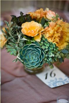 Interesting mix of colors and textures with the addition of succulents in this arrangement.