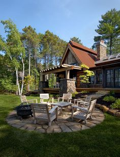 This cabin-style home is suited for year-round entertaining. A covered porch, an expansive lawn and a fire pit can be used whether there's sun or snow. Many readers saved this photo for the beautiful stonework in the fire pit area.
