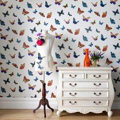 Behang FlutterBy van Graham & Brown is rijkelijk versierd met vlinders in een caleidoscoop van kleuren. Dit opvallende ontwerp is verkrijgbaar met een zwarte of witte achtergrond, beiden bestrooid met glitters.