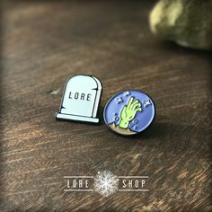A 2-pack of gorgeous enameled lapel pins. Show off your love of all things  Lore with a bit of spook on your coat or bag. This set features the Lore  gravestone and the zombie hand, because...well...why not?