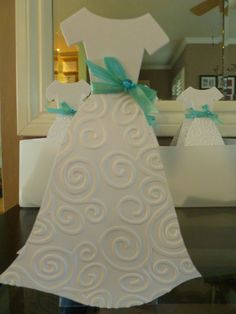 I made these for a bridal shower that was cinderella/tiffany blue color theme. There are two dresses back to back with a box of candy in between. The brides version had a tulle skirt and v neck lined with rhinestones. I alternated with a candy bar favor - see separate pin