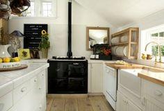 Dish rack,  farmhouse sink, gooseneck faucet, vintage stove, pot rack, and beautifully rustic floors