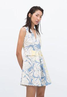 Vestido entallado con cuello en pico, manga sisa y bolsillos delanteros, de Zara.